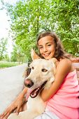 Portrait of nice teen girl with her dog sitting on the bench in sunny summer park poster