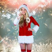 Pretty girl in santa outfit pointing against cream snow flake pattern design poster