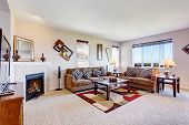 White living room with fireplace and colorful rug. Furnished with brown couches and coffee table poster