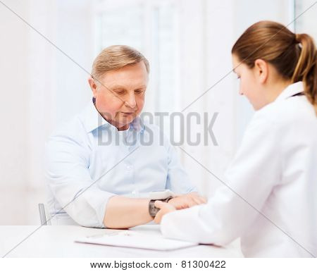 healthcare, elderly and medical concept - female doctor or nurse with male patient measuring blood pressure