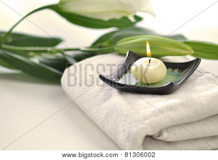 Scented candle and flowers placed on white towel - spa objects