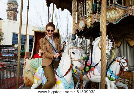 Attractive young woman having fun riding on carousel in amusement park during his holidays