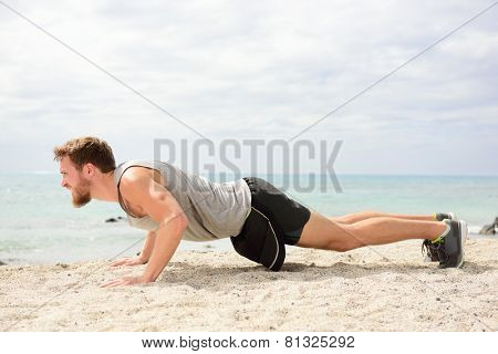 Push-ups - man fitness model training pushups on beach outdoors. Fit male fitness trainer working out exercising in summer on beach.