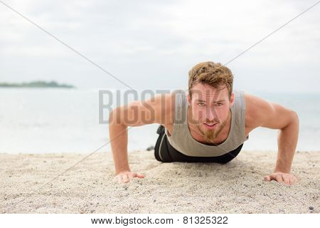 Push-up crossfit man fitness model training pushups on beach outdoors. Fit male fitness trainer working out exercising in summer on beach. poster