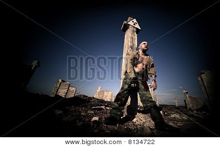Bloody zombie in the military uniform under the radiation sign on the ruined buildings background. poster
