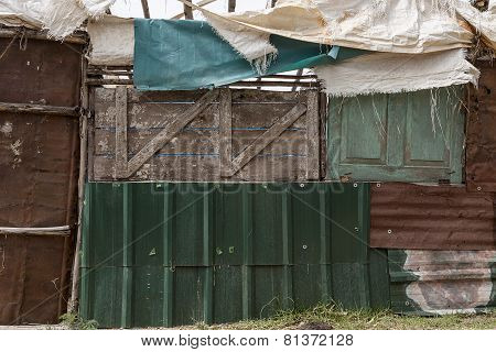 Side of a cabin built with recovered materials metal sheets and wooden planks
