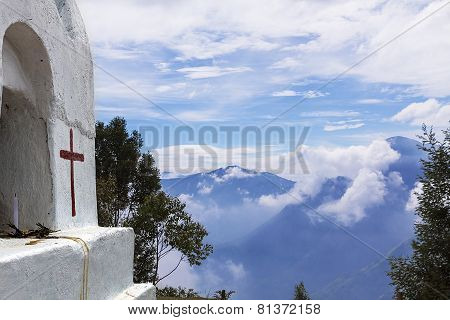 Detail of a small site of prayer built at high altitude with a peaks of mountains on the background