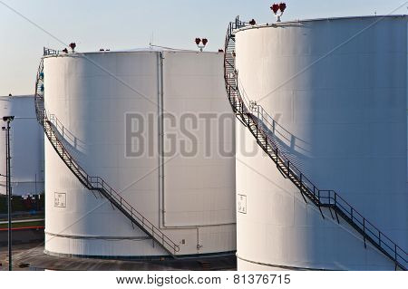 white tanks in tank farm with blue clear sky poster