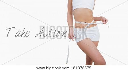 Midsection of slim woman measuring waist over white background