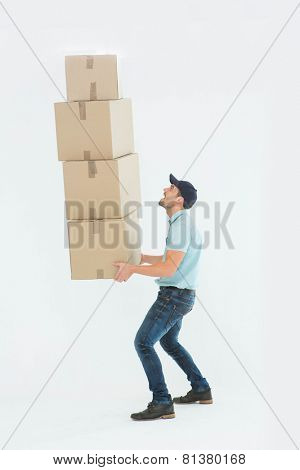 Full length side view of shocked delivery man carrying stack of boxes on white background