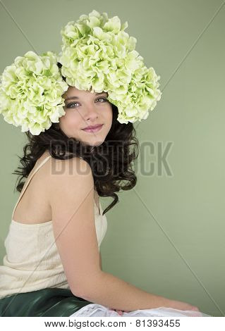 Pretty teenage girl with large green flowers in her hair