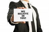 Businessman in a suit holding up a business card with motivational message We believe in you. poster