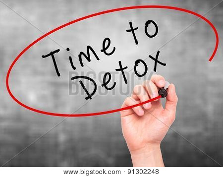 Man Hand writing Time to Detox with marker on transparent wipe board