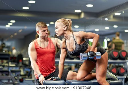 fitness, sport, exercising, bodybuilding and weightlifting concept - young woman and personal trainer with dumbbells flexing muscles in gym poster
