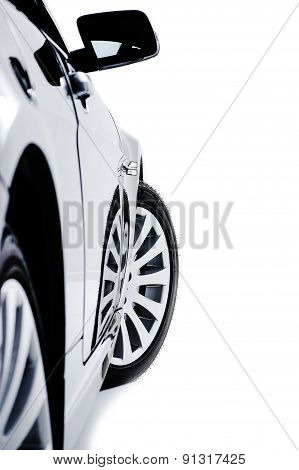 Side bodywork of a modern black car with alloy sport wheels and a protruding wing mirror viewed down the length of the vehicle isolated on white poster