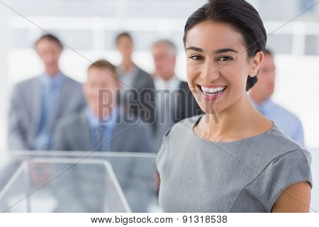 Smiling businesswoman looking at camera during conference in meeting room poster
