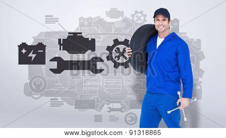 Confident mechanic carrying tire against grey vignette
