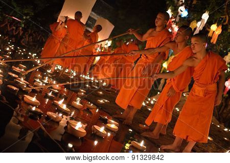 Thai monk with traditional lamp