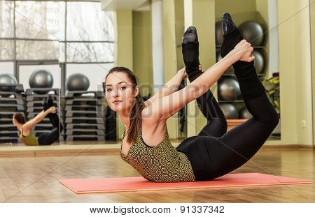 Young flexible woman in a yoga stretching bow pose poster