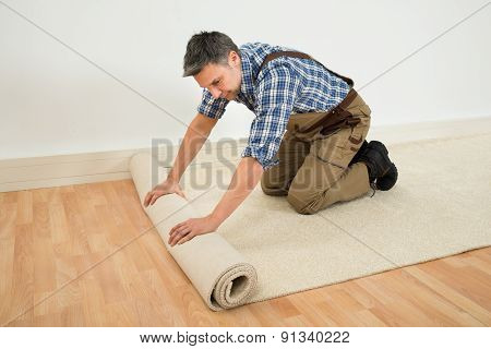 Worker Unrolling Carpet On Floor