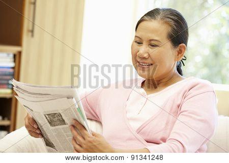 Senior Asian woman reading newspaper