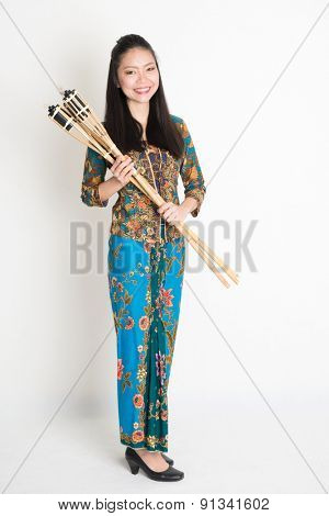 Full body portrait of Southeast Asian girl in batik dress hands holding oil lamp torch standing on plain background.