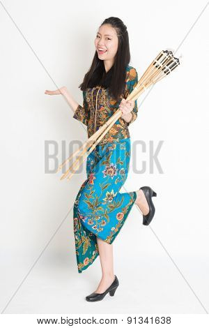 Full body portrait of happy Southeast Asian woman in batik dress hand holding bamboo oil lamp standing on plain background.