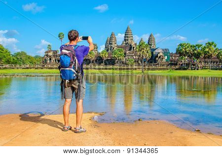 Young man is taking a photo of Angkor Wat temple