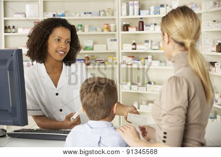 Pharmacist in pharmacy with mother and child poster