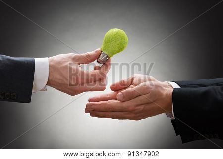 Businessman Giving Eco Light Bulb To Other Businessperson