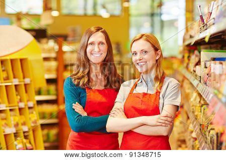 Two friendly saleswomen smiling in a supermarket with her arms crossed