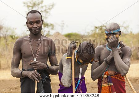 Boys And A Man From Mursi Tribe With Spears In Mirobey Village. Omo Valley. Ethiopia.
