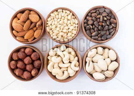 Six types of nuts in a round wooden form (almonds hazelnuts pine nuts cashews pistachio) on a white background poster