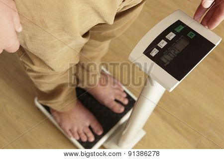 Man standing on digital scales cropped waist down