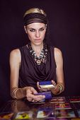 Fortune teller forecasting the future with tarot cards on black background poster