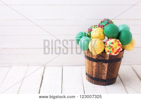 Cake pops in decorative bucket on white painted wooden background. Selective focus. Place for text.