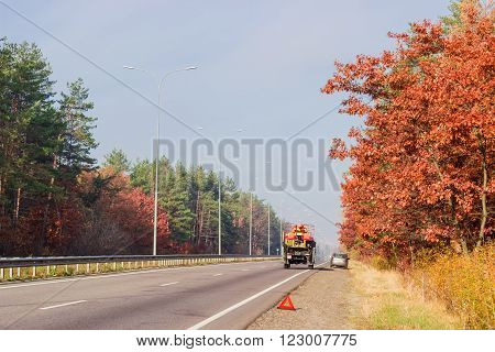 Standing vehicle and warning triangle on sidelines of the asphalt motorway with road marking lampposts traffic barriers and forest on both sides autumn morning