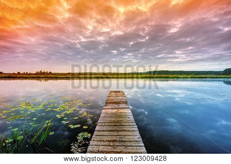 Wooden boards pier on Calm Water Of Lake, River at Sunset time, Forest On Other Side. Landscape. Nature Background.