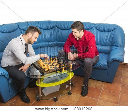 Two friends playing chess on a blue couch.