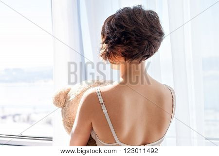 A girl with short hair in a bra back to camera looking out the window and holding a soft toy bear. Bright sunny day.