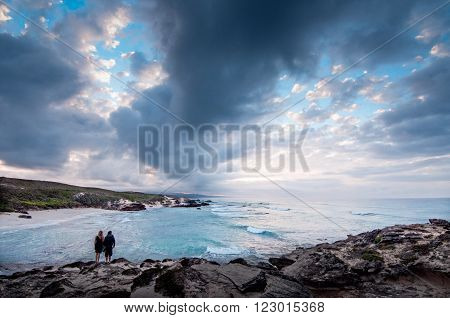 A couple standing at the ocean edge of a bay with a dramatic stormy sky overhead.