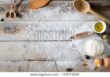 Making pie: Dough, rolling-pin and wheat flour on wooden table
