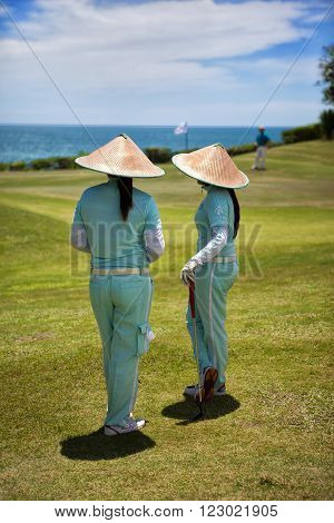 BALI, INDONESIA Two caddies with straw hats on a golf course near Tabanan  In Indonesia, caddies are always women.