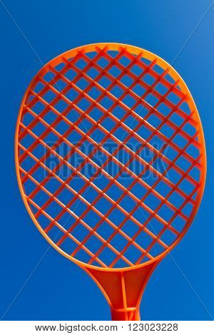 Orange Racquet in the sun fronting a blue sky