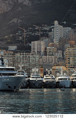 Monte Carlo, Monaco - September 20, 2015: yachts modern vessels at moorage in sea port on sunny summer day against mountains on cityscape background, vertical picture