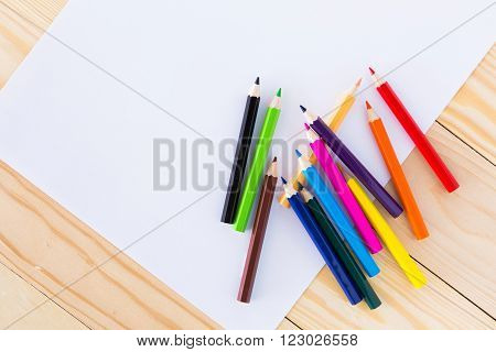Colorful crayons on a sheet of lined white paper.