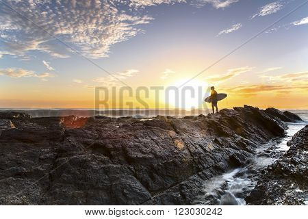 GOLD COAST, AUSTRALIA - JANUARY 2 2016: Silhouette of a surfer standing at the end of Currumbin Rock Gold Coast, at sunrise