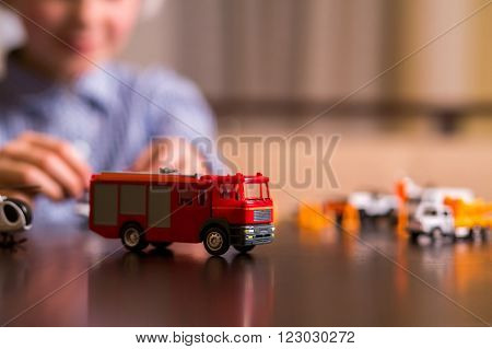 Toy fire truck on table. Close-up of toy fire truck. The heaviest vehicle. This one is very different.