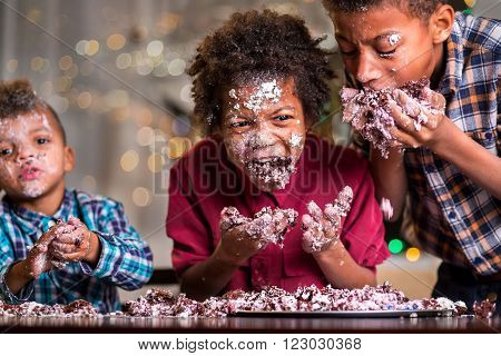 Afro kids greedily eating cake. Three boys devour small cake. Welcome to our humble party. Celebrating together is fun.