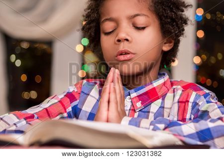 Afro child praying. Black kid prays beside window. Boy's evening prayer. Gesture of faith.